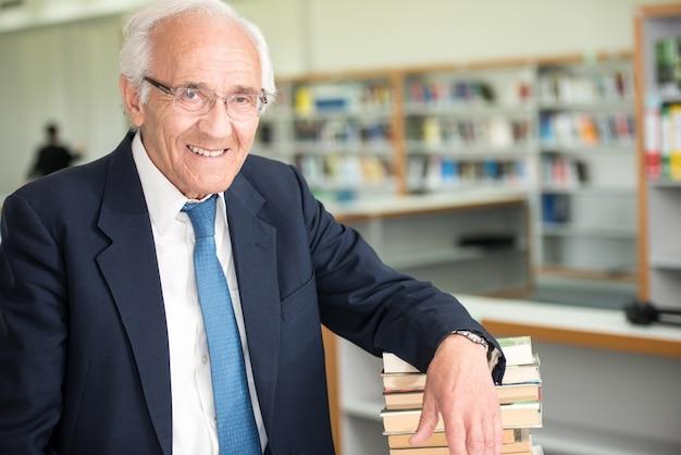 Professor idoso com livros dentro da sala da biblioteca da faculdade