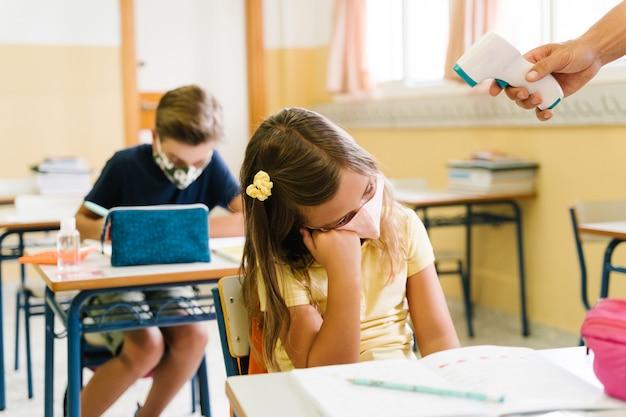 Professor medindo a temperatura de uma menina em sala de aula com um termômetro durante a terrível pandemia. ela está doente e com febre, ela tem a doença cobiçosa.