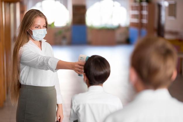 Professor medindo temperatura corporal na escola