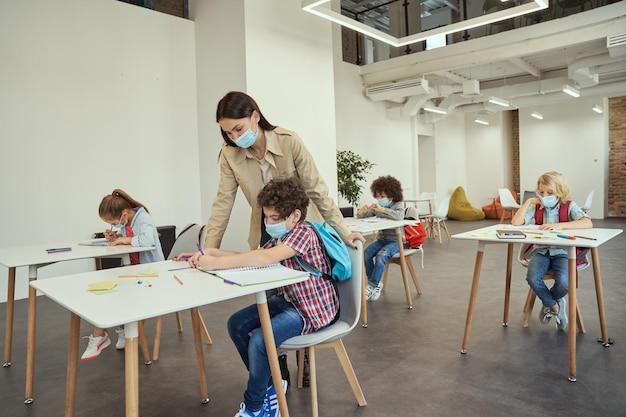 Professor moderno usando máscara protetora, ajudando o garotinho durante a aula de crianças estudando em