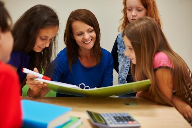 Professor mostrando aos alunos um livro interessante
