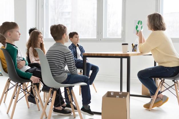 Professor, mostrando as crianças como reciclar