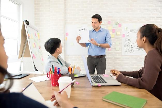 Professor mostrando e explicando o exemplo no papel para o grupo de estudantes universitários