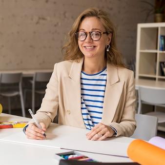 Professor na mesa escrevendo