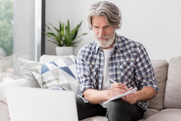 Professor, olhando para o laptop e anotando
