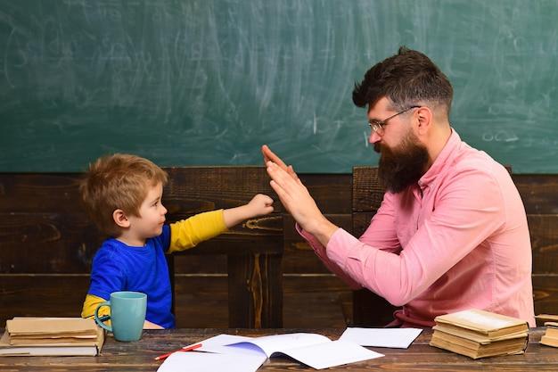Professor pai e aluno bonito criança brincando na sala de aula.