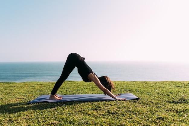 Professor praticando ioga ao ar livre em frente ao mar. copie o espaço