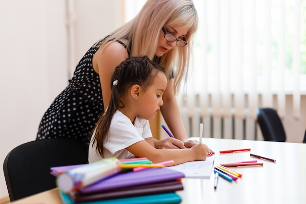 Professor pré-escolar novo que ensina meninas na sala de aula