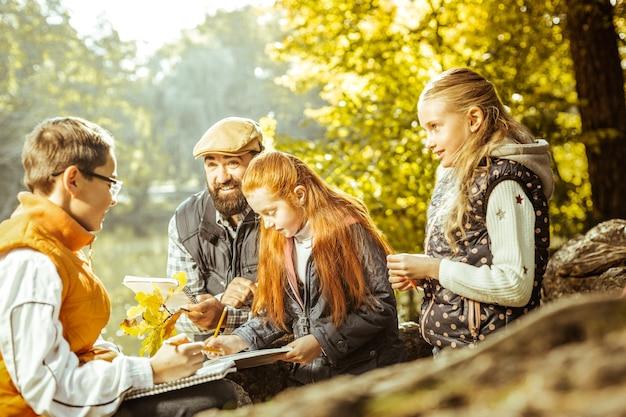 Professor profissional dando uma aula de ecologia para seus alunos na floresta em um dia bom