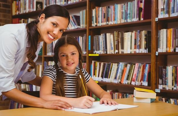 Professor que ajuda garotinha com lição de casa na biblioteca