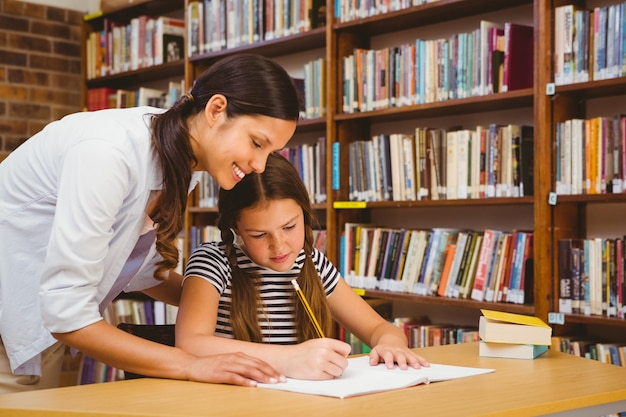 Professor que ajuda menina com lição de casa na biblioteca
