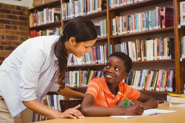 Professor que ajuda o menino com a lição de casa na biblioteca Foto Premium