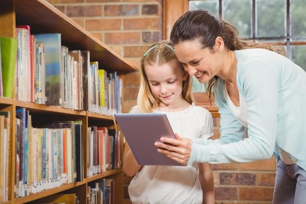 Professor que ajuda um aluno a usar um tablet