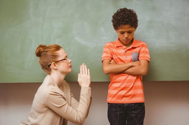 Professor que se desculpa com um menino na sala de aula