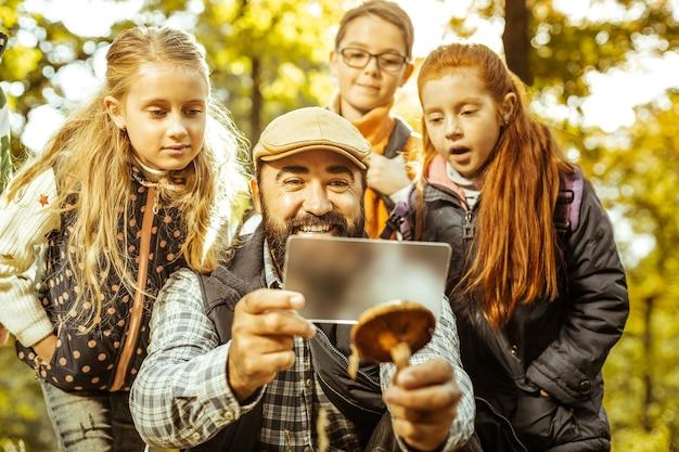Professor segurando cogumelo para seus alunos verem na floresta em um dia bom