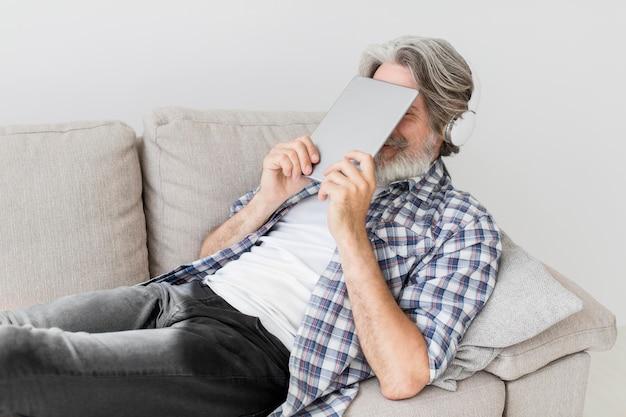 Professor, segurando o tablet perto do rosto
