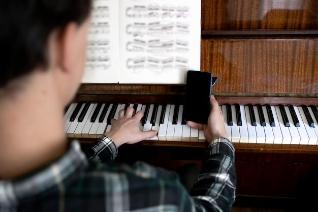 Professor segurando seu telefone durante a aula de piano online