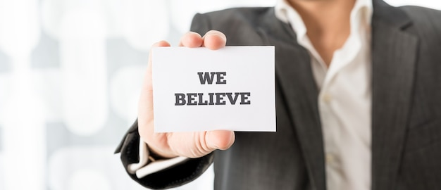 Professor segurando um cartão branco com o símbolo nós acreditamos nele, close-up no formato de banner horizontal de sua mão.