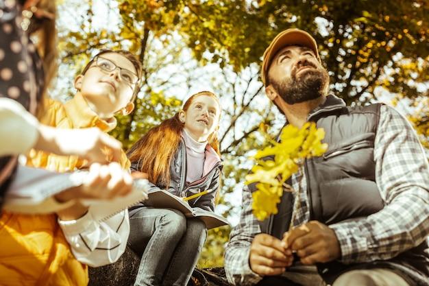 Professor segurando um galho de árvore e contando a seus alunos sobre ecologia em um dia ensolarado