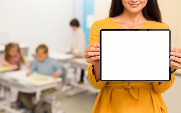 Professor segurando um tablet na sala de aula