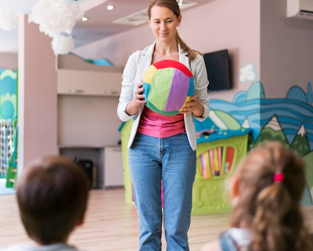 Professor segurando uma bola colorida