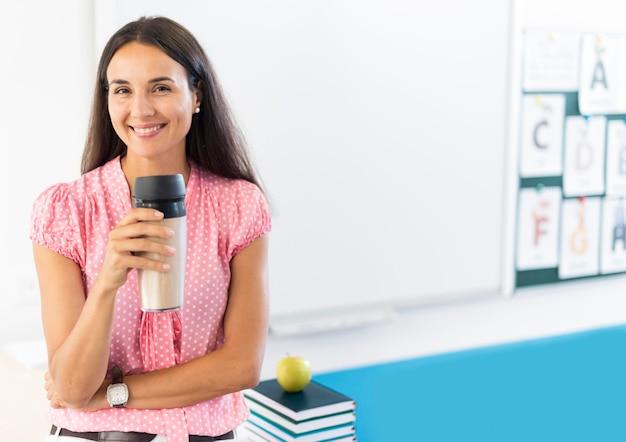 Professor segurando uma garrafa térmica com espaço de cópia