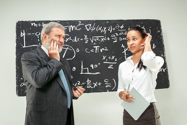 Professor sênior masculino e jovem aluna contra o quadro-negro em sala de aula. conceito de emoções humanas. modelos caucasianos. educação, faculdade, universidade, palestra, escola, conceitos de aprendizagem