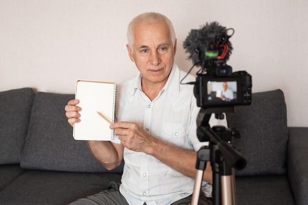 Professor sênior mostrando algo no caderno fazendo um vídeo para palestra em casa