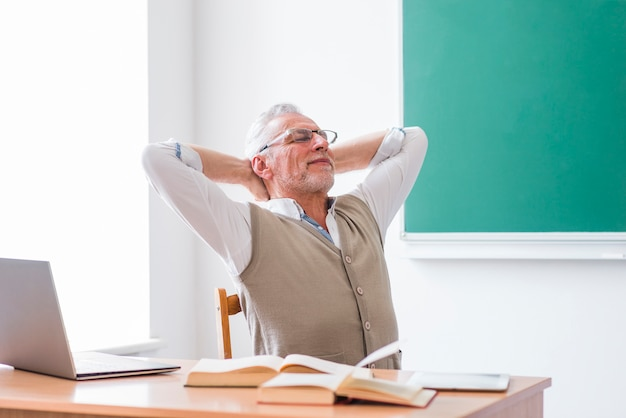 Professor sênior, sentando, em, sala aula, com, mãos cabeça
