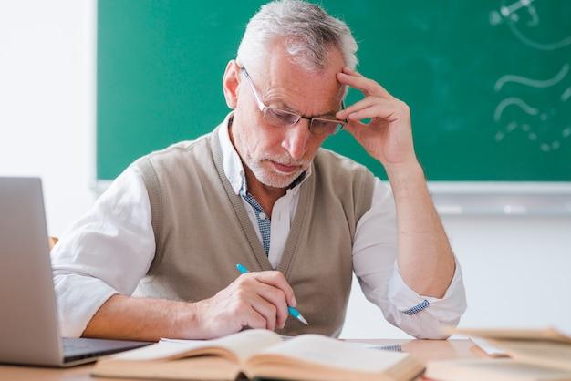 Professor sênior, tocar, templo, enquanto, caneta segurando, em, sala aula