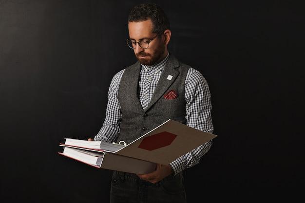 Professor sério e barbudo, com camisa xadrez oxford e colete de tweed, usando óculos, lê o plano educacional em duas grandes pastas de documentos para seu aluno no próximo ano na universidade