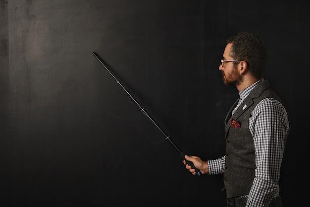 Professor sério e barbudo, de camisa xadrez e colete de tweed, usando óculos, mostra algo no quadro preto da escola com seu ponteiro dobrável