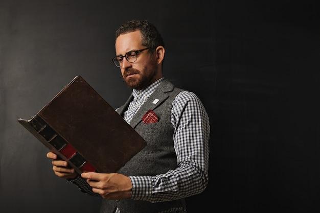 Professor sério usando colete de tweed e camisa xadrez lendo um grande livro antigo em um quadro negro