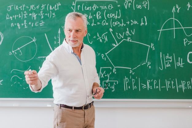 Professor sociável do sexo masculino em pé no quadro-negro e apontando à mão