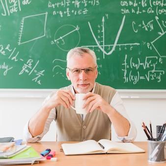 Professor sorridente com bebida em sala de aula