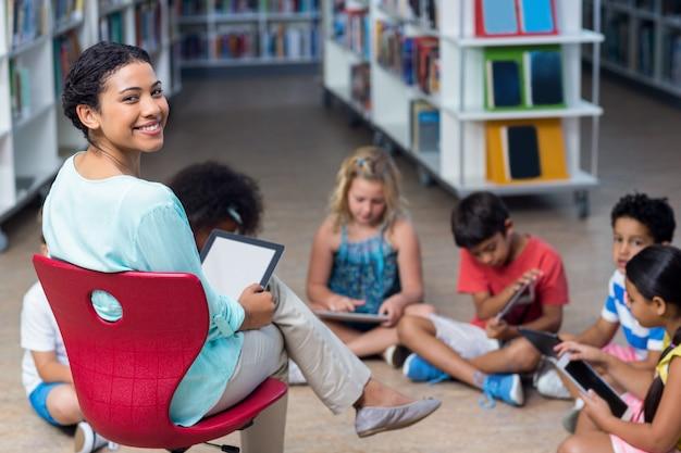Professor sorridente com crianças usando tablets digitais
