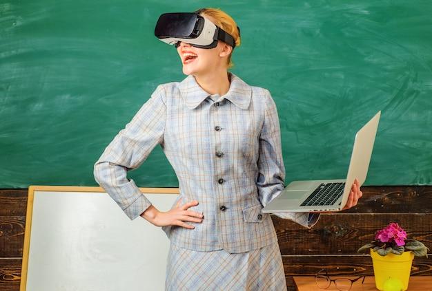 Professor sorridente com laptop em fone de ouvido vr. educação digital. tecnologias modernas na escola inteligente. tutor feliz em sala de aula.