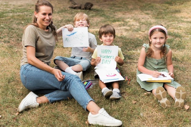 Professor sorridente de alto ângulo e crianças ao ar livre