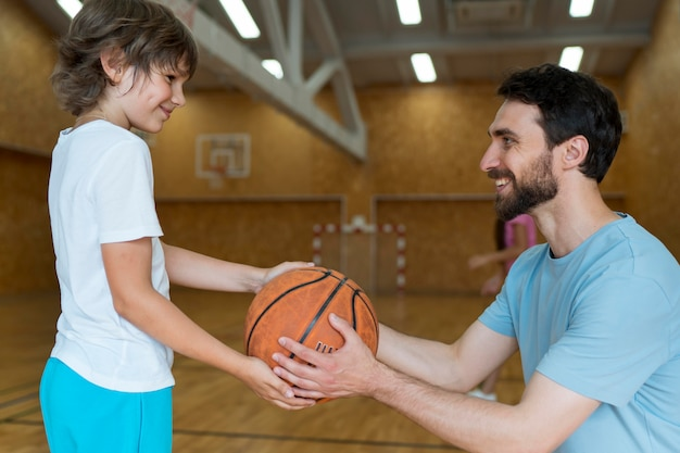 Professor sorridente de tiro médio e criança com bola de basquete