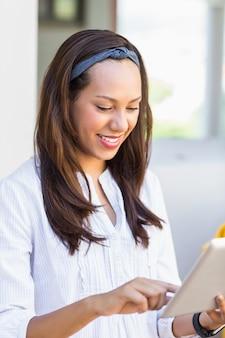 Professor sorridente usando tablet digital em sala de aula