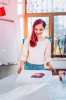 Professor sorrindo. uma bela professora de arte ruiva sorrindo e se sentindo satisfeita com sua pintura