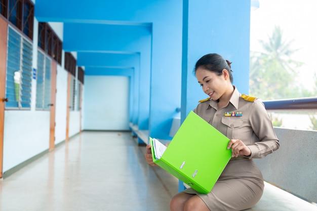 Professor tailandês com roupa oficial está verificando a pasta de arquivos