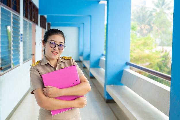 Professor tailandês sorridente com roupa oficial de pé e segurando pastas de arquivos