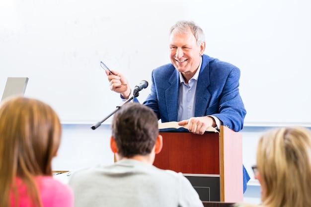 Professor universitário dando palestras para alunos sentados na mesa