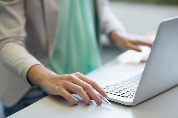 Professor, usando o laptop na biblioteca