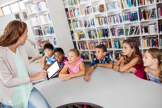 Professor usando tablet com alunos
