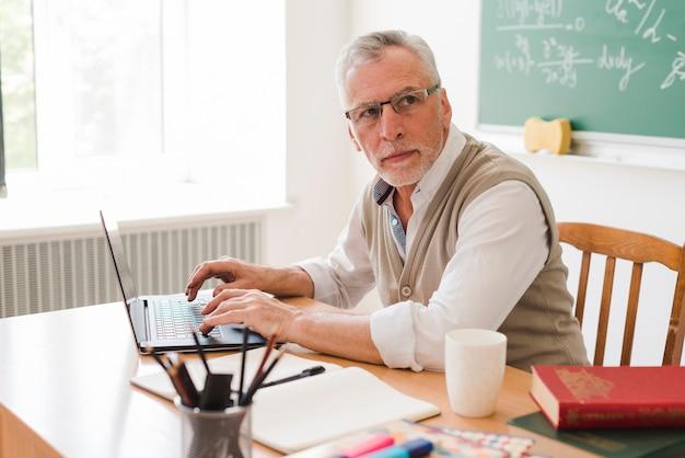 Professor velho inteligente usando laptop em sala de aula