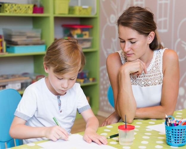 Professor vendo criança desenhando