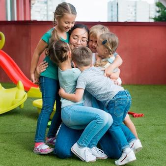 Professora abraçando seus alunos