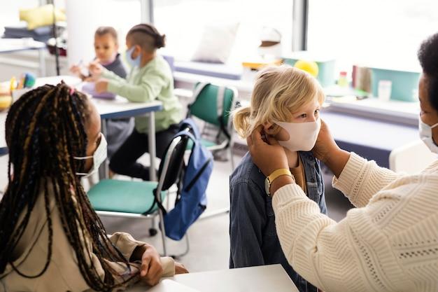 Professora ajudando crianças com suas máscaras médicas
